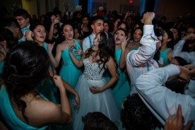The quinceanera on the dance floor all night surrounded by friends and family