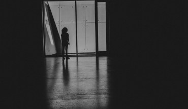 A black-and-white silhouette of a woman standing at the end of a hallway, facing away from the camera.