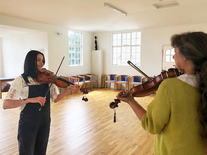 Ros & kirstie playing fiddle in the hall at Kilcreggan