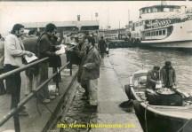 """Le Pont Galata à Istanbul. On nous vend des sandwich au poissons qui sont grillé sur le barbecue installé sur la barque. On aperçoit au fond, les """"vapeurs"""" qui desservent les Iles. Dommage qu'on puisse pas entendre les aboyeurs et le bruit de fond de l'ambiance.. Lieu magique. Même avec des vagues, les serveurs et le barbecue continue plein pot , Sur la photo, Serge Baguès et Maurice Macedonia (en blanc)"""