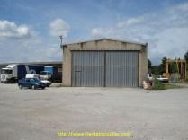 A gauche, les quais encore utilisés, au centre le portail de l'ancien atelier, sur la droite et derrière, le parking