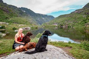 Anna and three dogs next to a lake in Lofoten Islands
