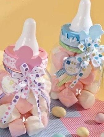 Decoración de centros de mesa con biberones llenos de dulces azul y rosa