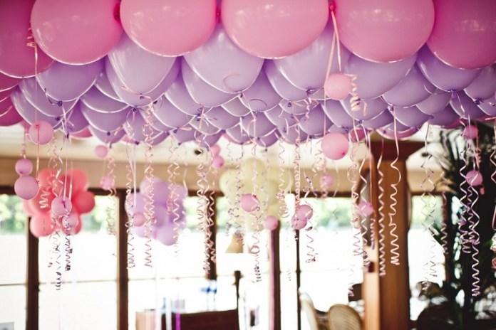 Hermosa Decoración de globos en el techo con colores lila y rosa