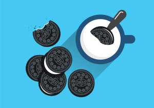Black and white Oreo cookies one being dunked into a glass of milk on a blue background