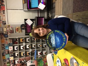 Woman with dark brown hair in blue sweater and blue jeans holding painting painted on LP record.