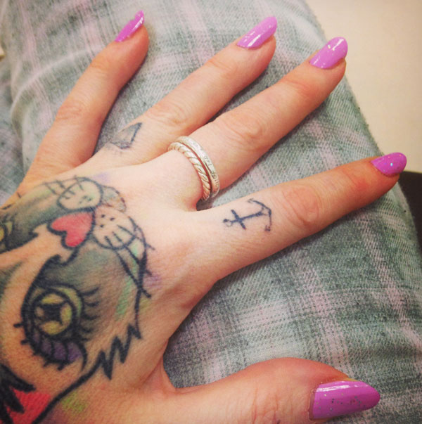 Hester – showing their hand, with pink painted fingernails and a tattoo of a cat, on light jeans.