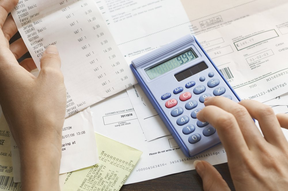Woman calculating expenses using a calculator