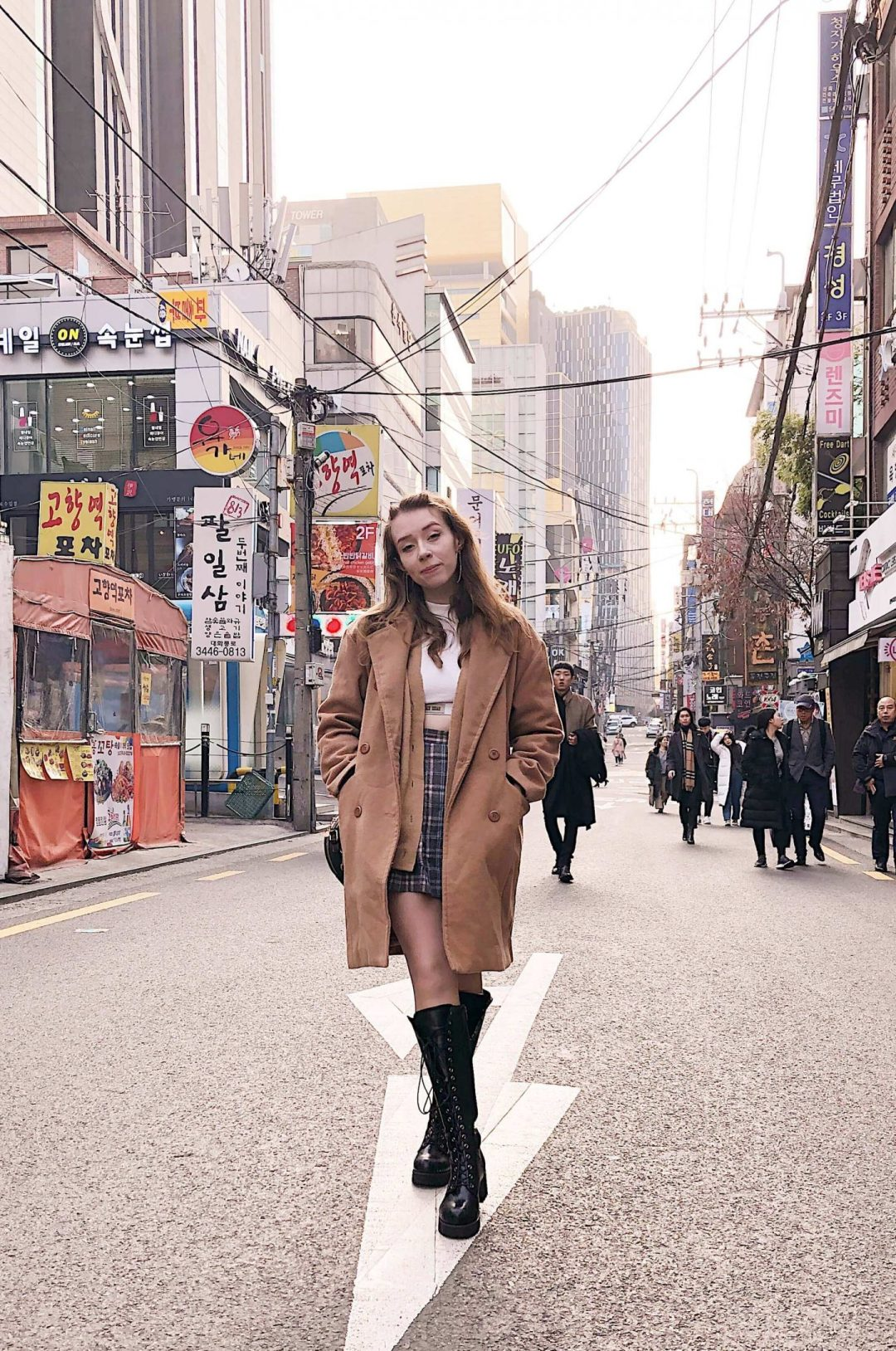 Fii is standing in the middle of the road facing the camera, with tall buildings either side and some people behind. She is wearing the same outfit as above and almost smiling at the camera.