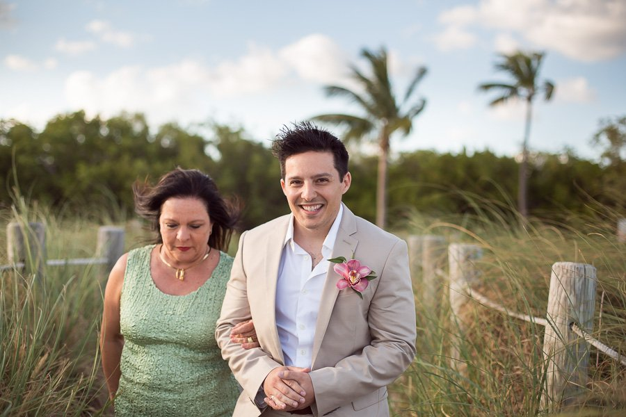 groom walking down the isle with his mom key wets wedding photographer
