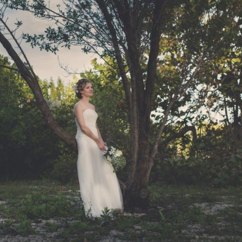 bride with bouquet sits on the tree in key west florida