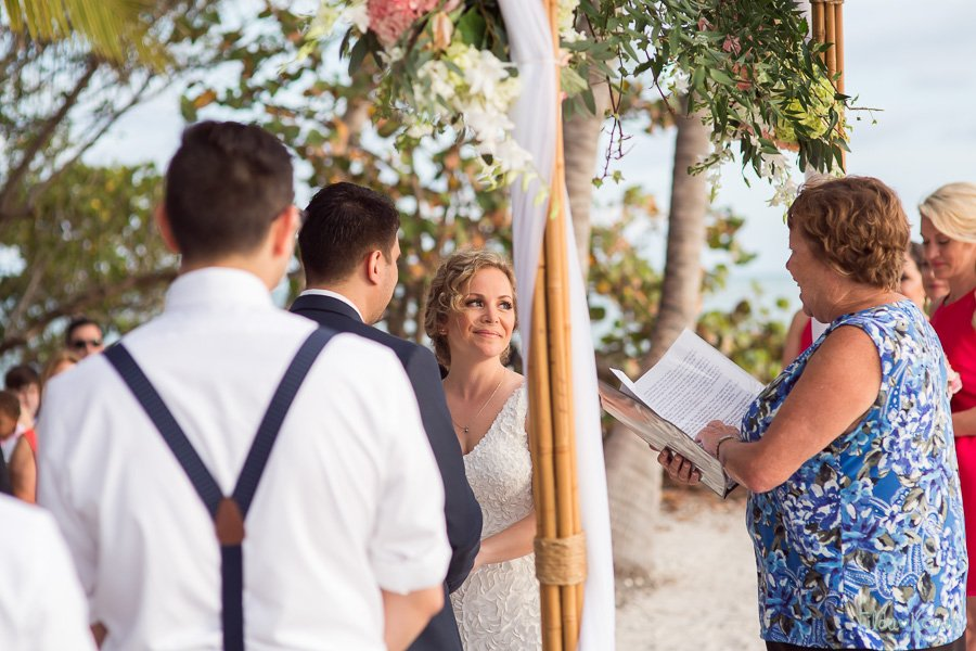 bride looking at officiant during beach ceremony