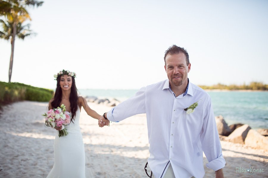 groom leading his bride on sand near the ocean at sunset key