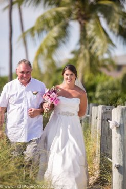 father walk his daughter to the altar for her beach wedding