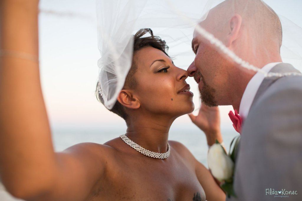 Wedding couple is about to kiss under the veil