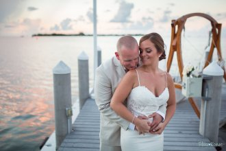 bride and groom hug on the dock at hyatt in key west during sunset