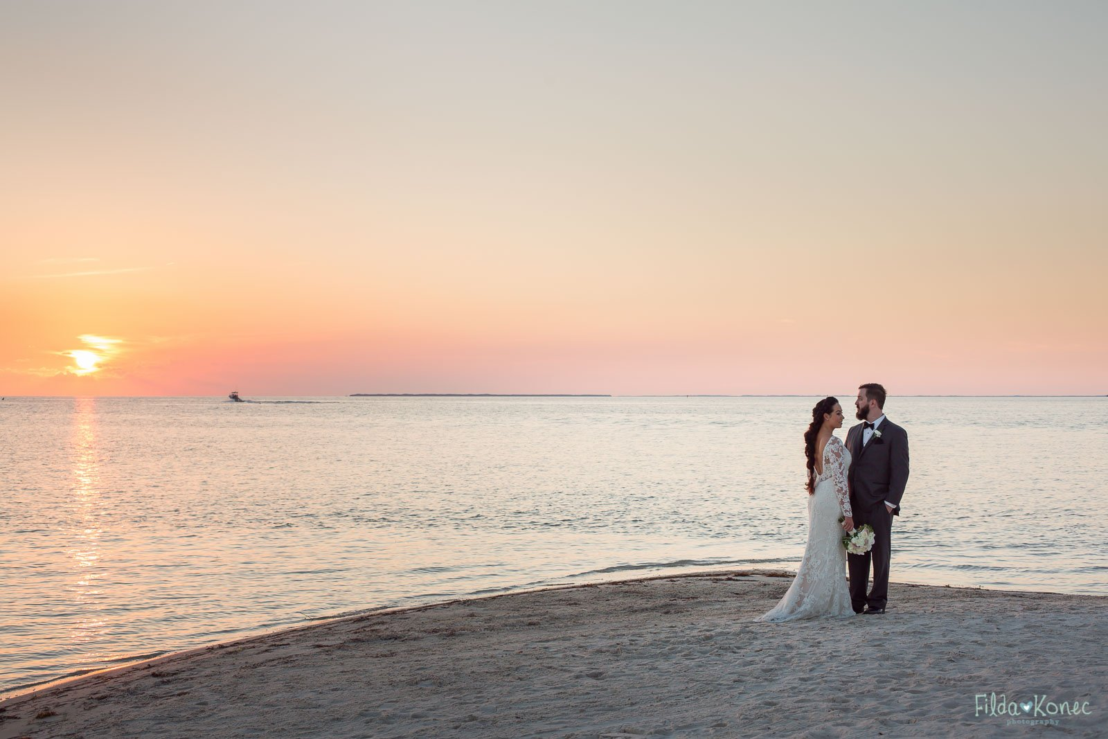 bride and groom watch beautiful sunset on the beach