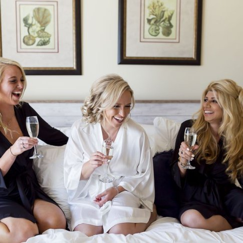 bride and bridesmaids laughing on the bed