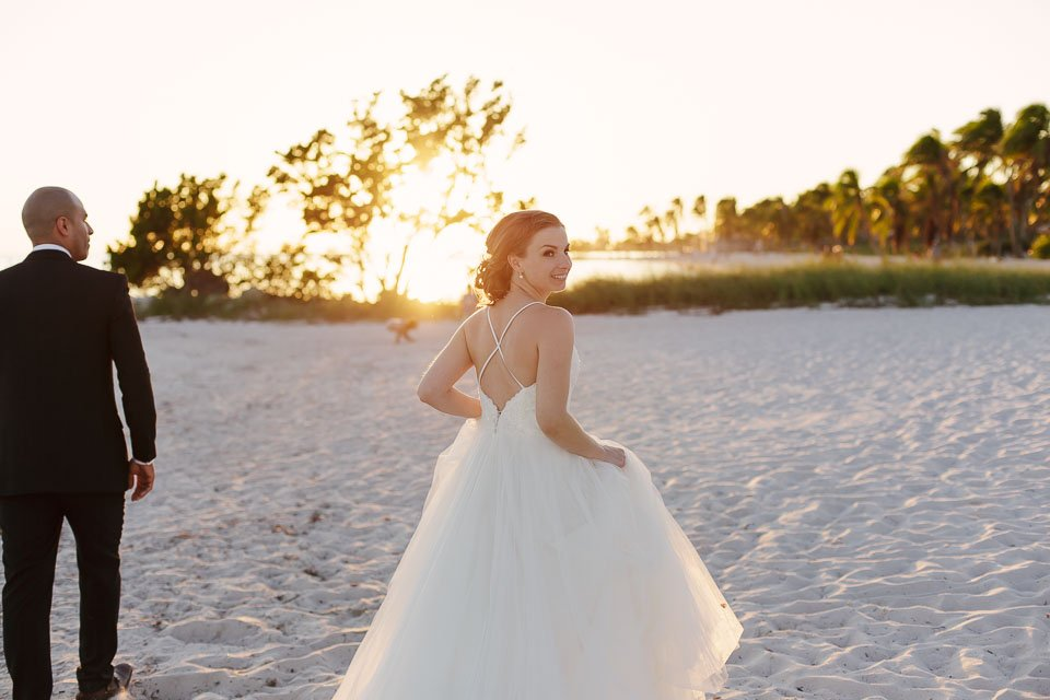 bride looks over her shoulder with sunset in the background