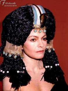 Parrucca in paglia azzurra con aspide ed accessori dorati indossata da un'attrice