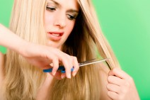 woman cutting hair with scissors