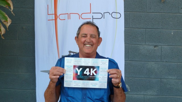 "Band Pro President, Amnon Band holding a ""Y4K"" flyer outside of the exhibition."