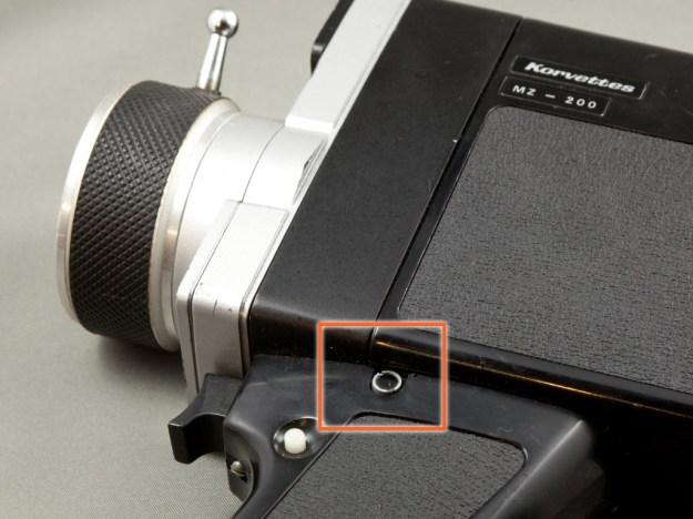 """Gut versteckt: Hier verbirgt sich eine von vier Schlitzschrauben, die den Handgriff befestigt. Das schwarze Blechplättchen an der japanischen """"Korvettes"""" Kamera muss vorsichtig abgehebelt werden, um den Schraubenschlitz freizulegen.  Wer Wert auf gute Optik legt, kann es später mit einem Tropfen Loctite oder auch Doppelklebeband dort wieder befestigen."""