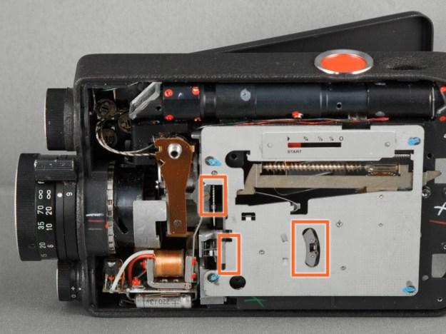 Sollte die Kamera quietschen oder zäh anlaufen, empfiehlt sich eine vorsichtige Schmierung. Mit feiner Kanüle gebe man kleinstmögliche Mengen von z.B. Nyoil auf die bewegten Teile. Neben Zahnrädern und ggf. der Motorachse (links unten) sind das auch plan laufende Steuerhebel. Setzt man die Kamera nun vorsichtig in Betrieb, lassen sich alle bewegten Teile gut auf Funktion beobachten.