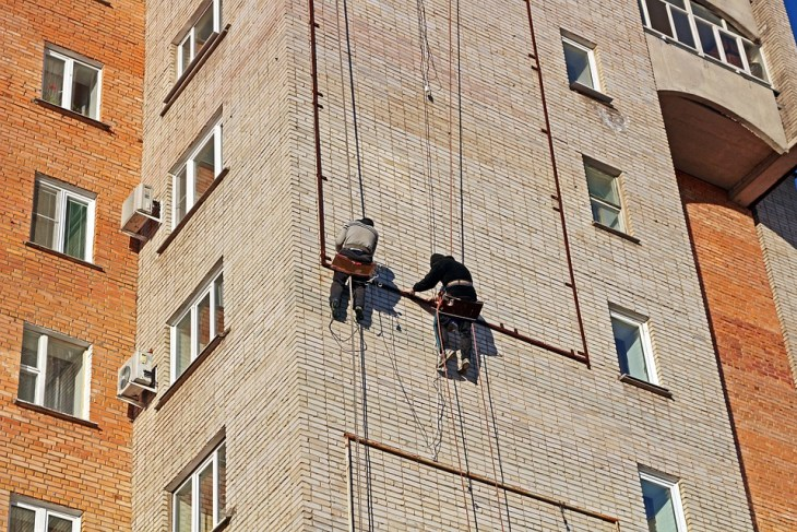 two guy installing poster frame on building wall
