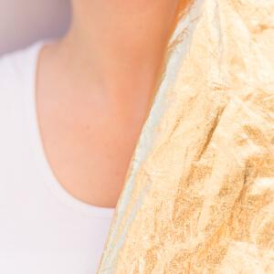 Goldene Folie an Haut mit weißen T-Shirt