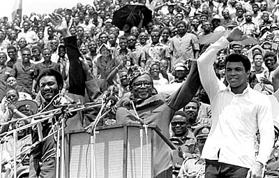 (NY16) (05/16/97_12.11_KINSHASAZAR) FILE--Zaire's President Mobutu Sese Seko, center, raises the arms of heavyweight champ George Foreman, left, and Muhammad Ali on Sept. 20, 1974. Ali defeated Foreman just over a month later during a world championship match.  Mobutu gave up power Friday, May 16, 1997, his information minister announced.  'He reigns but does not govern,'' Information Minister Kin-Kiey  Mulumba said at a news conference Friday. (AP Photo/Horst Faas)