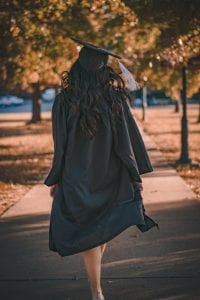 woman in black long sleeve dress standing on brown concrete pathway thinking about if a 529 plan is worth it