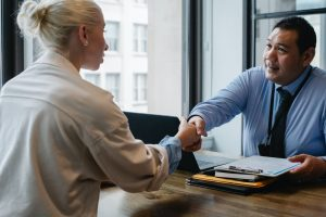 ethnic businessman shaking hand of applicant in office as a freelance recruiter