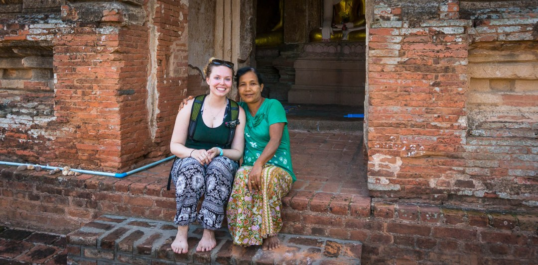 Hilary sitting with Burmese woman in front of temple
