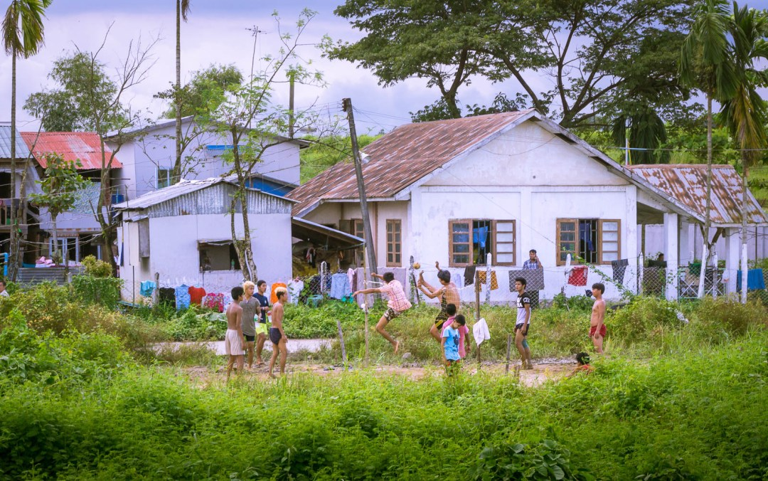 Young kids playing Chinlone in Myanmar beside village