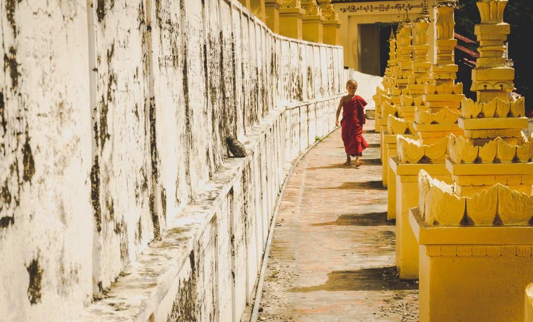Young monk walking among stupas