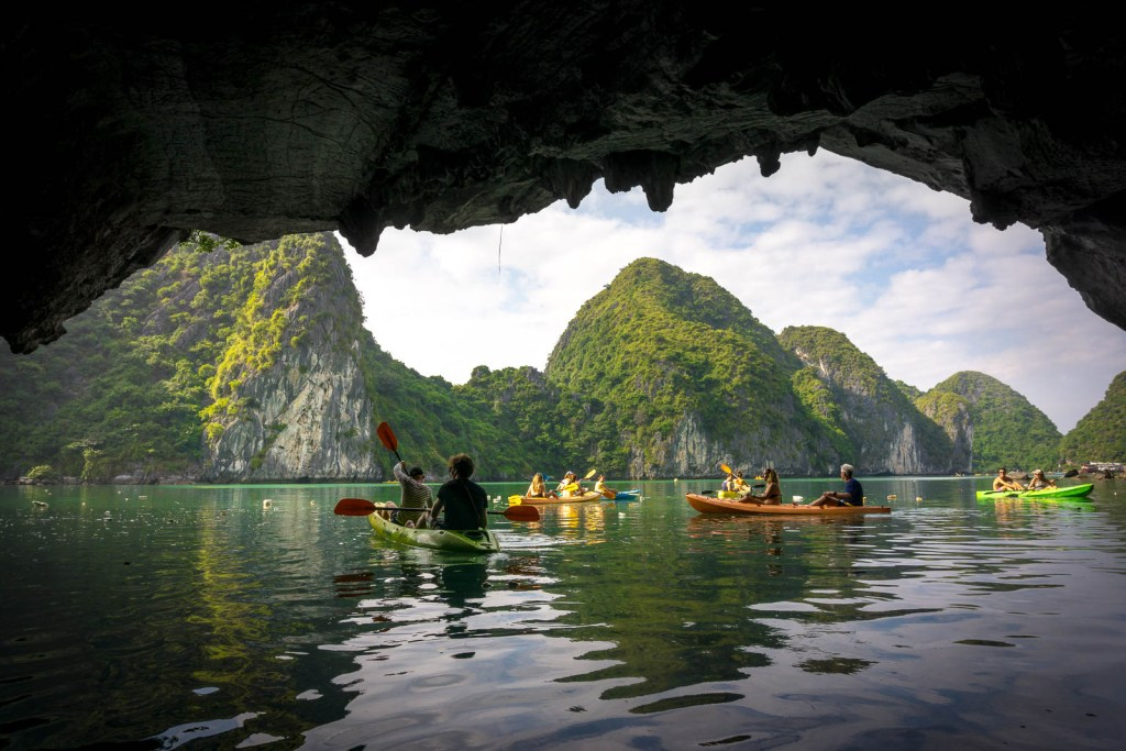 Kayakers going through cave in ha Long Bay