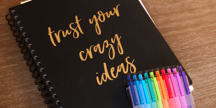 "Image of Imgy's Bullet Journal which is black with gold lettering that reads ""trust your crazy ideas"" and a pack of colorful pens."