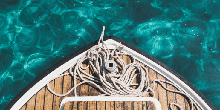 Aerial closeup view of bow of boat with ropes over rich turquoise water.