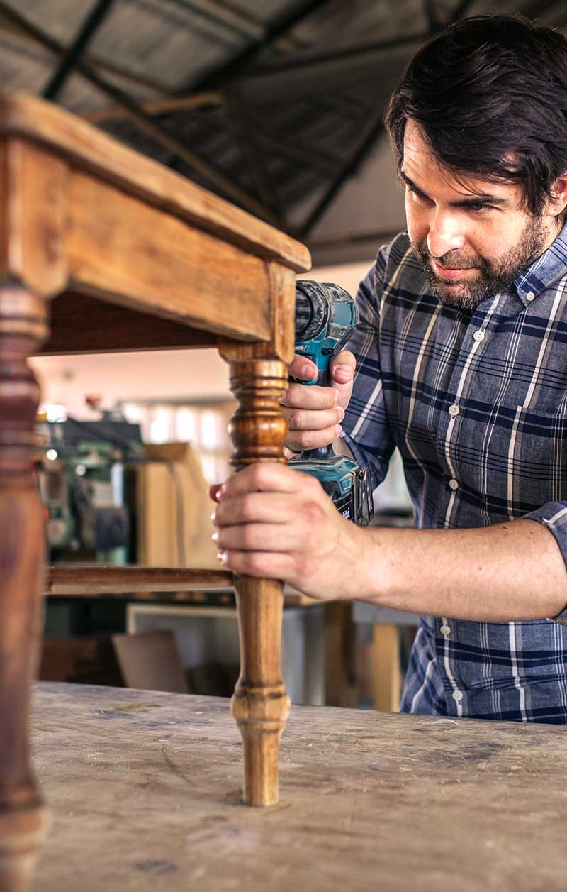 woodworker finishing a custom end table