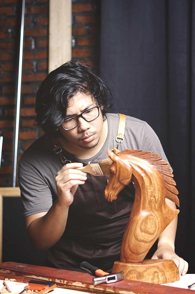 woodworker finishing a custom wood sculpture
