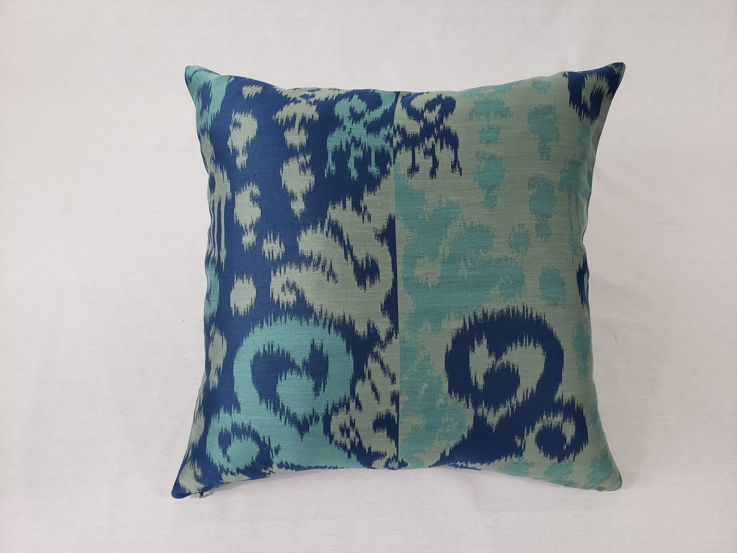A blue & green ikat patterned cushion