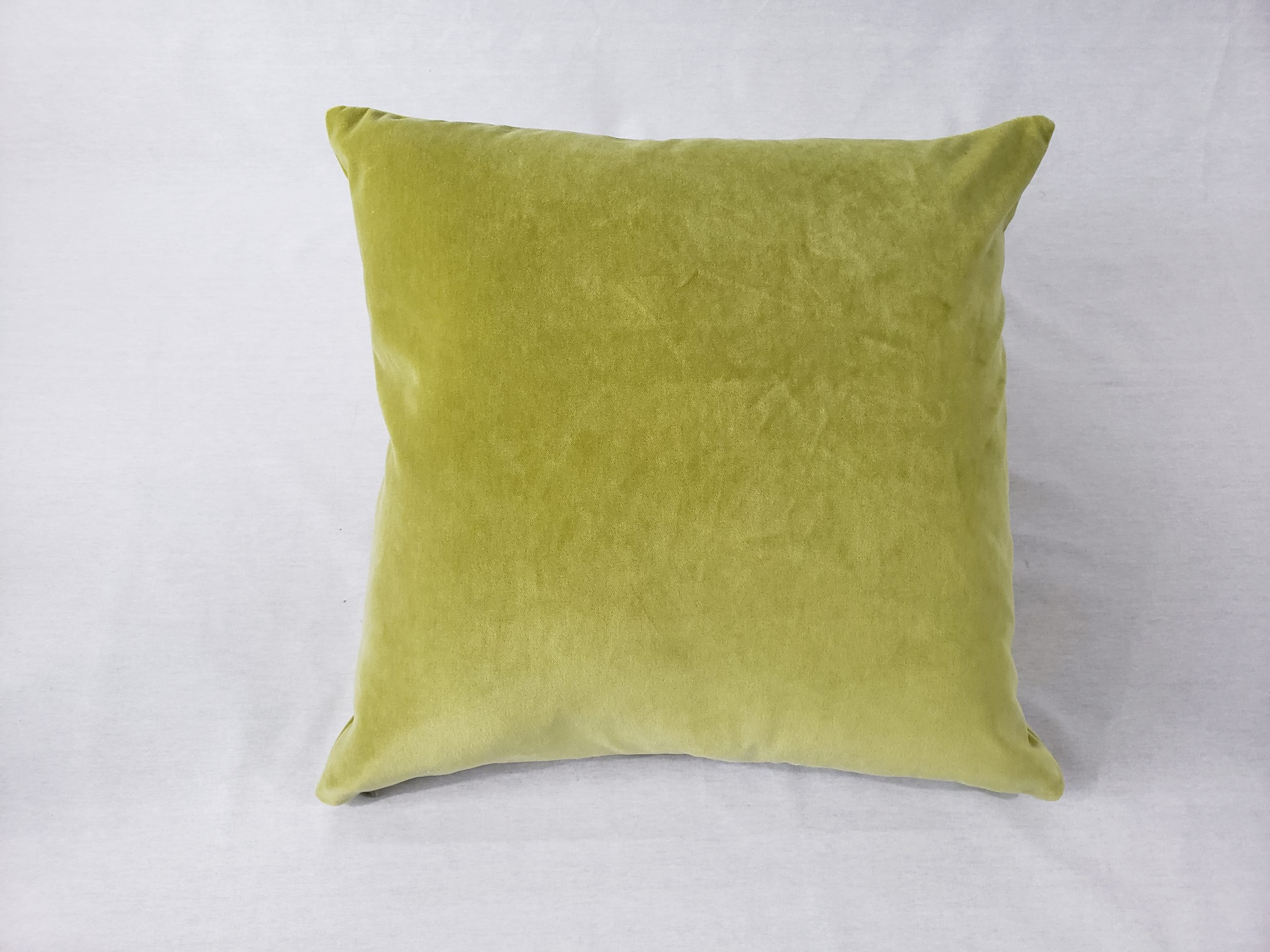 A lime green velvet cushion