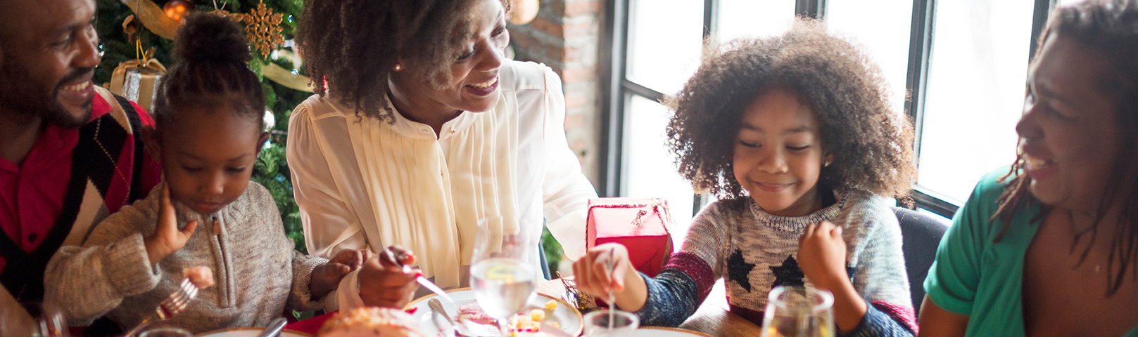 an african american woman laughs with her daughter during a holiday meal despite hearing loss