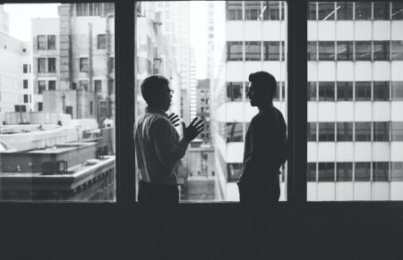 Clearcover CEO Kyle Nakatsuji and COO Derek Brigham stand backlit by at a large window in an office.