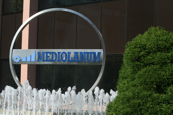The Italian bank Mediolanum store front positioned behind a fountain and greenery.