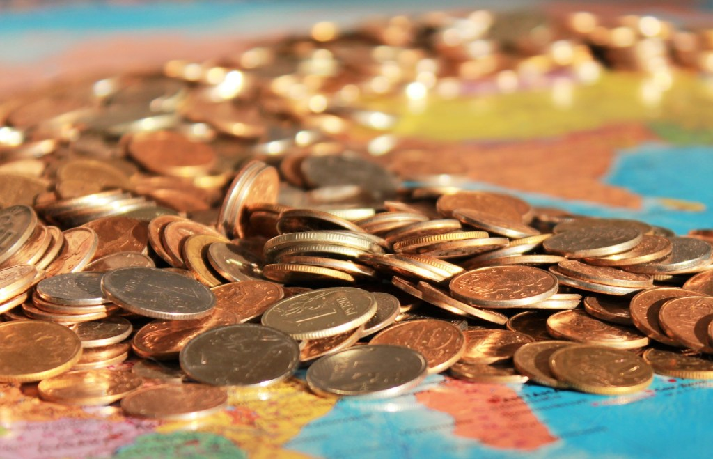 Pile of colorful coins on top of a map.