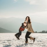 mom and kids play in the snowy mountains