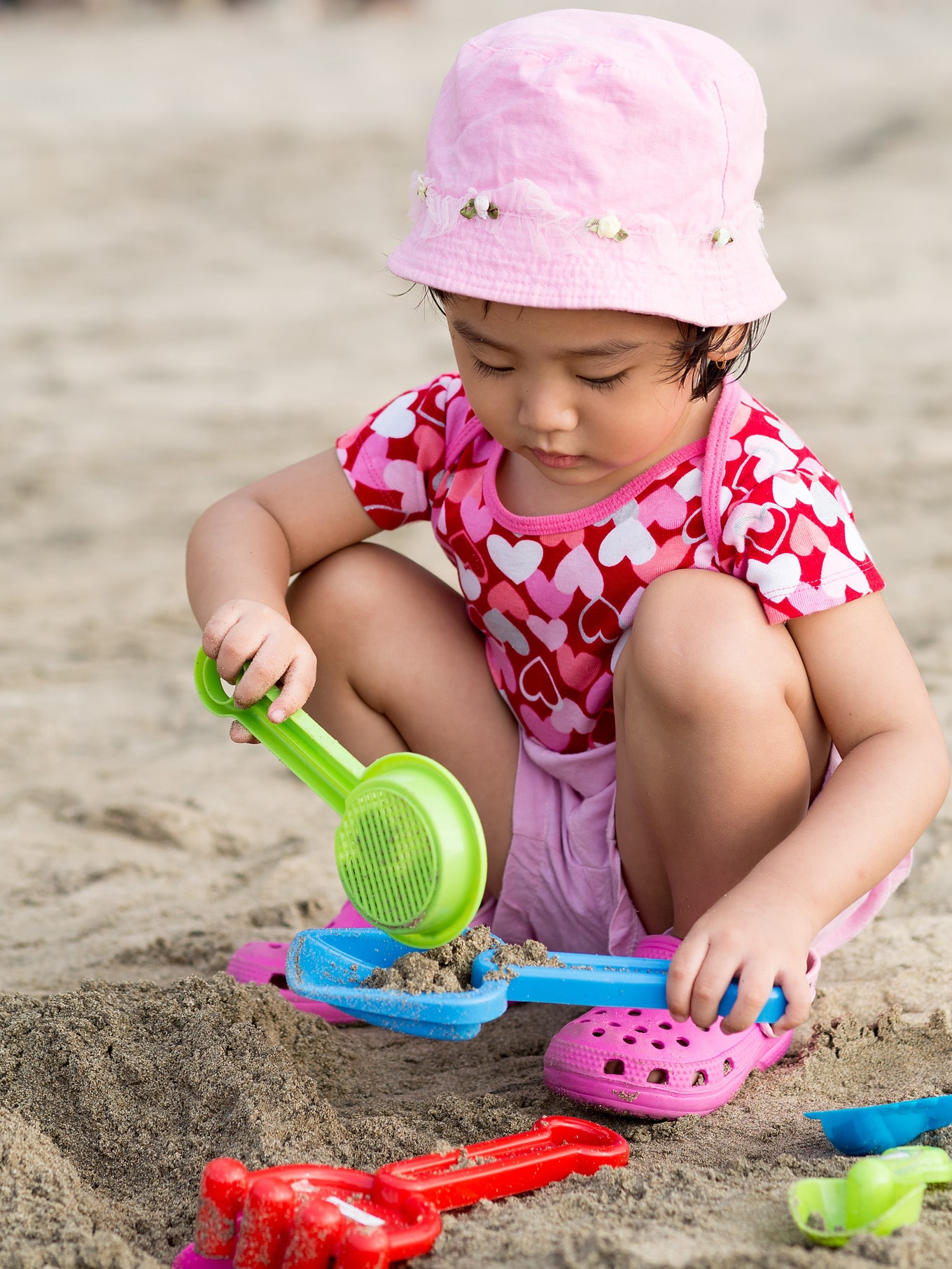 Child Playing on Beach with Sand Toys