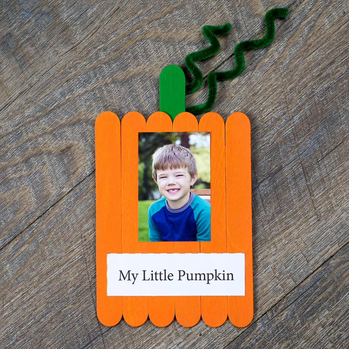 Completed Popsicle stick pumpkin keepsake with child's photo